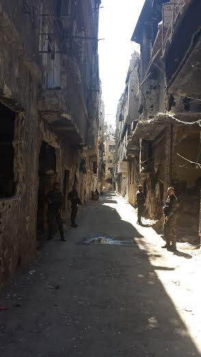 Palestinian fighters flank a corridor in Yarmouk on our way to visit refugees receiving aid.