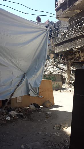 A sheet is draped in a Yarmouk passage to protect against snipers gaining visual targets.